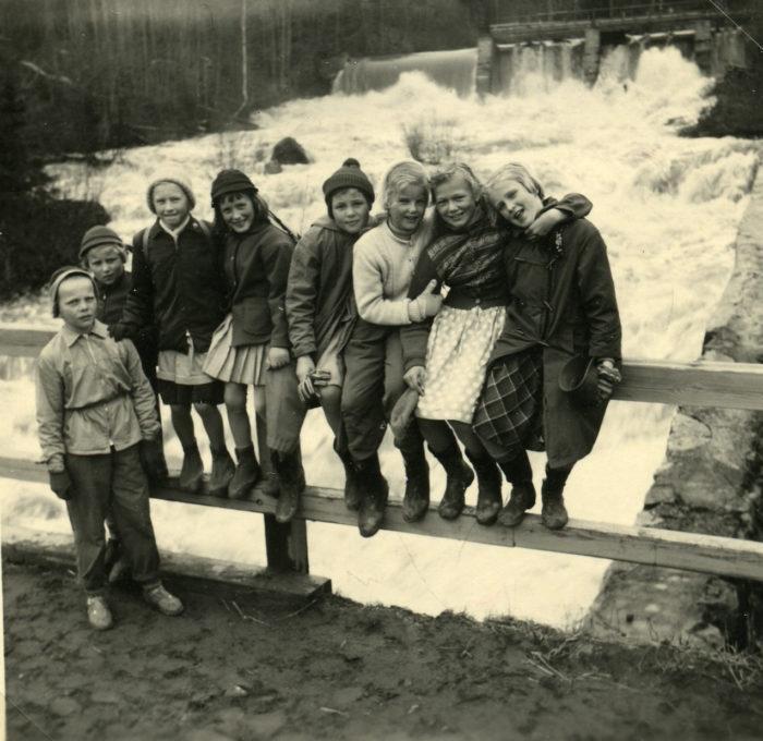 Luokkaretkeläisiä istumassa Myllykosken sillalla.