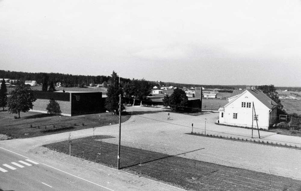 Kylänäkymä kirkonkylästä 1960-luvun lopusta. Risteyksen takana vasemmalla uusi kunnanvirasto, oikealla vanha kunnanvirasto Heikkari.