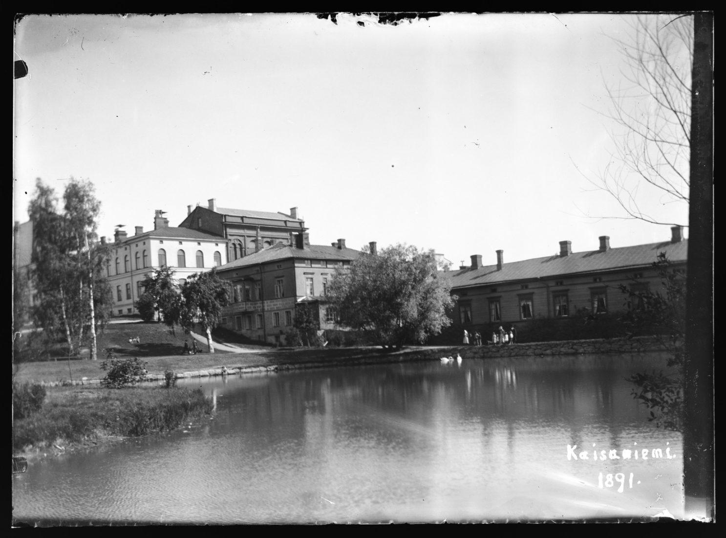 Kaisaniemi, Helsinki, joutsenlampi. Oikealla Villensauna eli Hotel Wilhelmsbad, hotelli ja kylpylä.