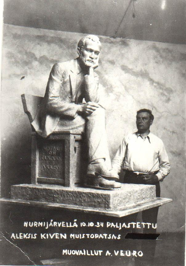 Kuvanveistäjä Aukusti Veuro seisoo veistämänsä Aleksis Kiven patsaan takana.