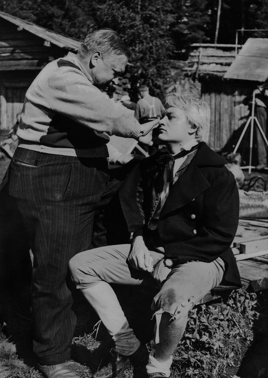 Nummisuutarit-elokuvan kuvaukset. Maskeeraaja Aarne Kuokkanen korjailee Eskon (Martti Kuningas) maskia. 1957