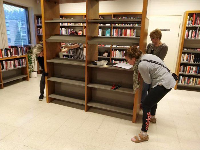 Neljä kirjastolaista siirtää kirjahyllyä.