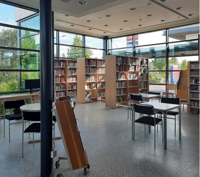 Pääkirjaston palvelupisteen sali. Kirjahyllyjä, tuoleja ja pöytiä.